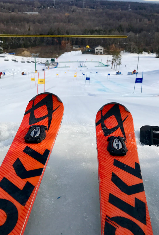 An image of orange skis at the top of a hill, waiting to push forward and about to race down a ski racing hill on snow.