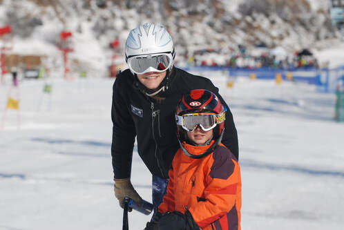 Picture of an adult ski racing coach and a young student, both dressed in ski gear, smiling for the camera.