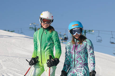 Image of two school age ski racers wearing their racing gear and smiling at the camera.